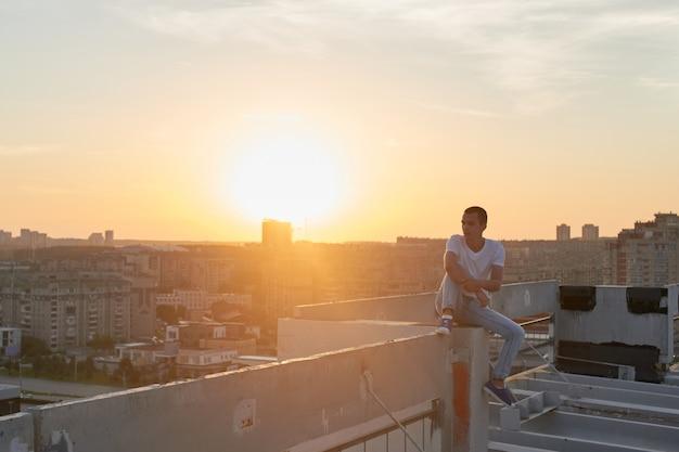 Le gars assis sur le toit et regardant le coucher du soleil