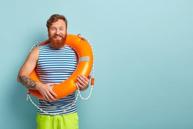 Un gars aux cheveux rouges barbu positif porte un gilet de marin rayé, porte une bouée de sauvetage orange
