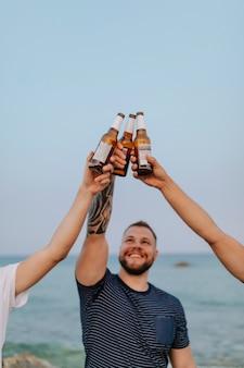 Les gars ayant des bières à la plage