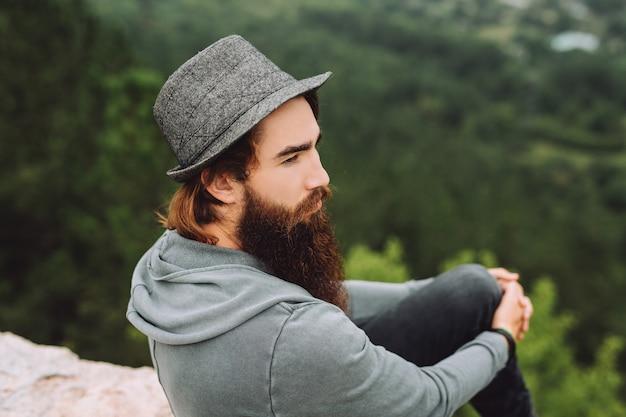Un gars barbu brutal regarde un regard perçant sur un beau paysage d'été.