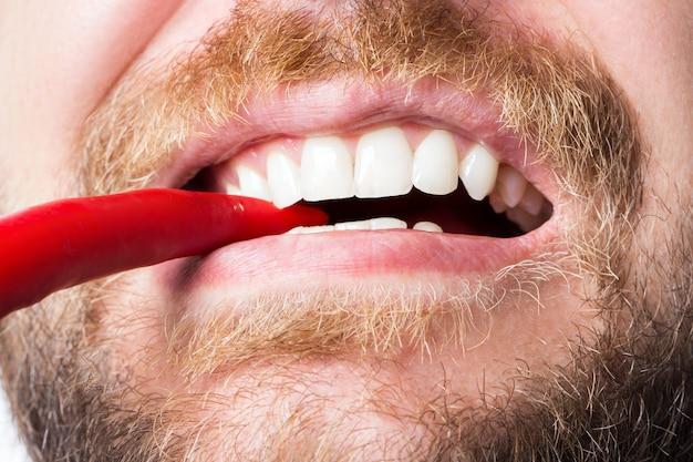 Un gars barbu avec un sourire blanc comme neige mord au piment rouge