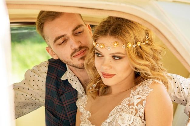 Un gars et une belle fille amoureuse sont assis sur le siège arrière d'une voiture