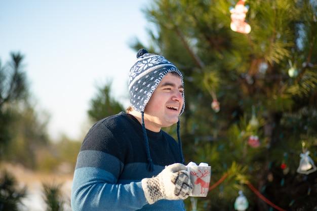 Le gars boit une boisson chaude avec des guimauves en hiver dans la forêt