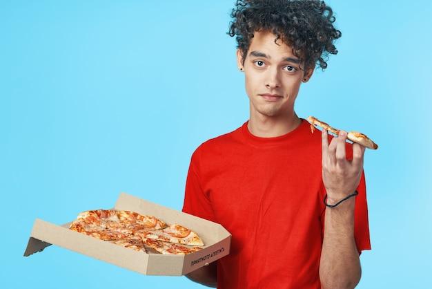 Gars bouclé drôle dans un casse-croûte de restauration rapide de livraison de pizza de tshirt rouge
