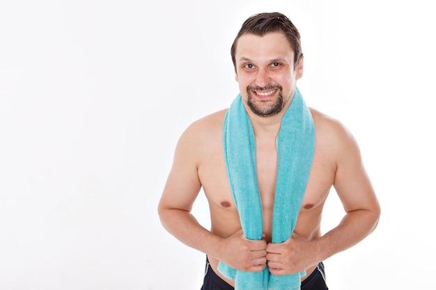 Le gars caresse sa barbe. soins du matin dans la salle de bain. serviette bleue autour de son cou. isolé sur fond blanc. copie espace