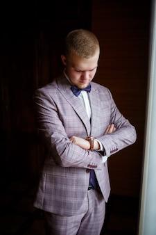 Un gars en chemise blanche et pantalon s'habille le jour d'un mariage.