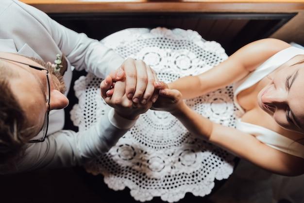 Un gars en costume et une fille en robe sont assis à la table et se tiennent la main et se regardent dans les yeux