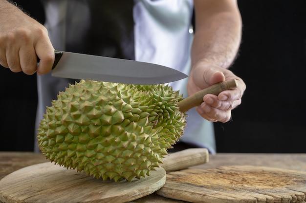Les gars coupent durain le roi des fruits sur fond en bois