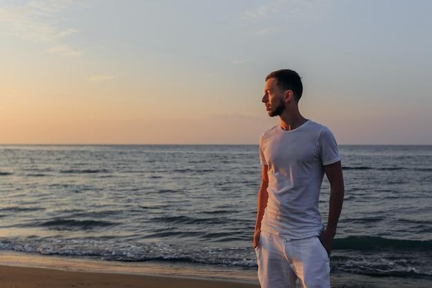 Un gars dans un t-shirt blanc et un short tient ses mains dans sa poche