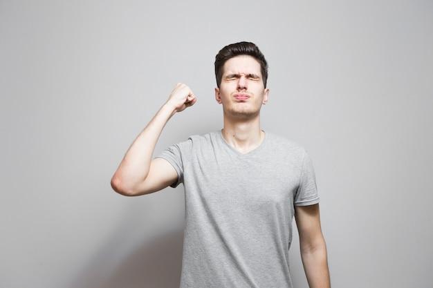 Un gars dans un t-shirt gris avec des émotions sur son visage.