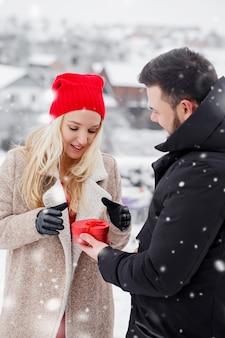 Le gars donne à la fille une boîte comme cadeau pour la saint-valentin