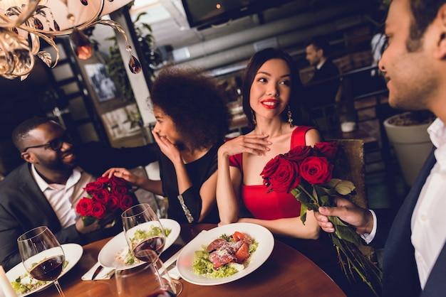 Les gars donnent des roses à leurs filles dans un restaurant.