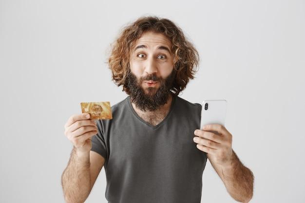 Un gars du moyen-orient barbu amusé et excité montrant une carte de crédit et un smartphone, passant commande