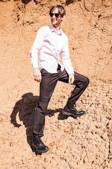 Gars élégant sur une carrière de sable