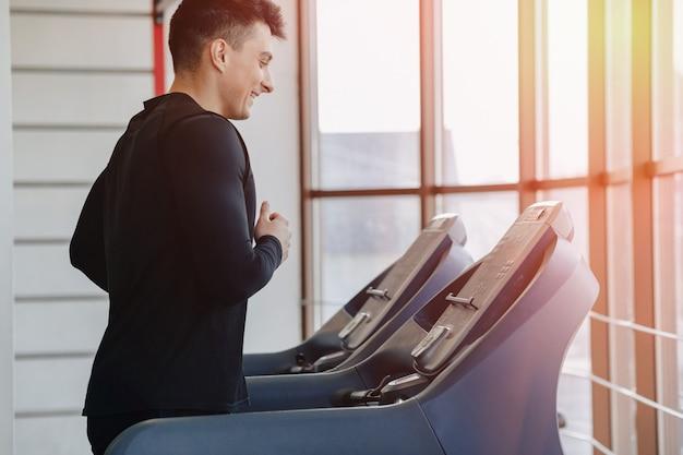 Un gars élégant dans la salle de gym s'entraîne sur le tapis roulant. mode de vie sain.