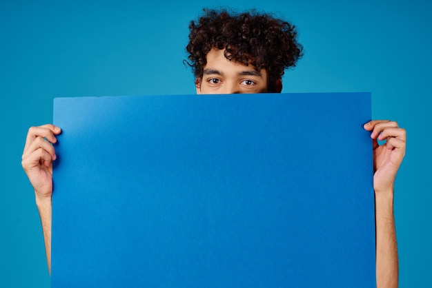 Le gars avec l'espace de copie publicitaire de l'affiche bleue