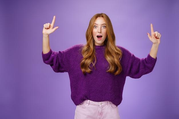 Les gars, c'est cool, vous ne pouvez pas imaginer. portrait d'une jolie jeune femme au gingembre excitée, surprise et impressionnée, en pull violet, levant les mains vers le haut, laissant tomber la mâchoire d'étonnement sur le mur violet.