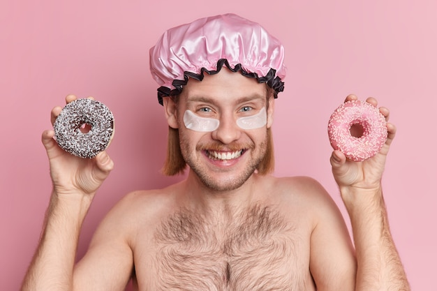 Un gars européen positif avec une expression heureuse applique des patchs de collagène sous les yeux tient des beignets sucrés porte un bonnet de douche à moitié nu