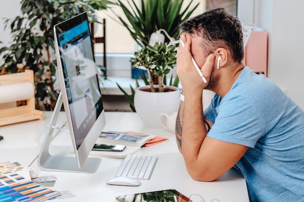 Un gars fatigué assis à table avec un ordinateur de bureau et d'autres appareils et outils de bureau. notion de surmenage.