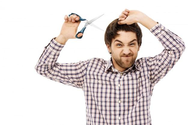 Un gars fatigué se coupe les cheveux en quarantaine, tient des ciseaux