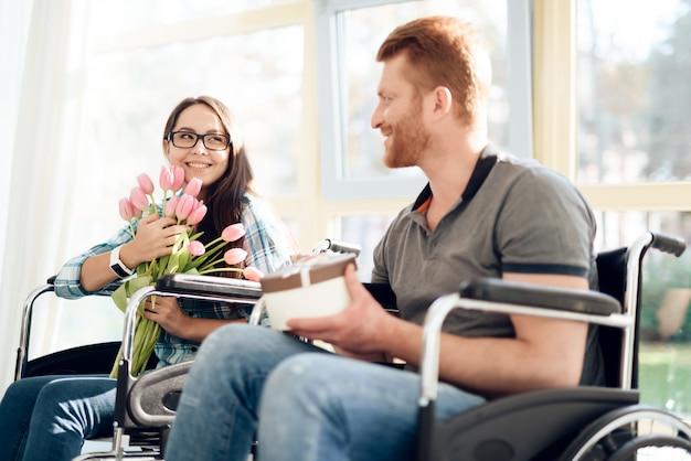 Un gars en fauteuil roulant a offert des fleurs et un cadeau à la jeune fille.