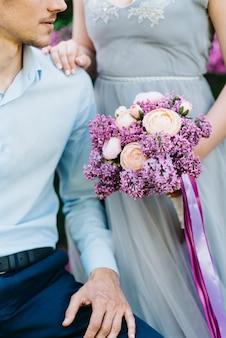 Un gars et une femme marchent dans le jardin printanier des lilas avant la cérémonie de mariage