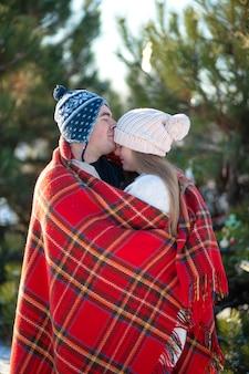 Le gars avec la fille embrassée enveloppé dans un plaid à carreaux rouge