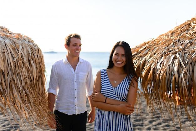 Le gars et la fille sur le fond de la mer. concentrez-vous sur la fille. devant eux, des bungalows. tourné sur la plage de santorin.