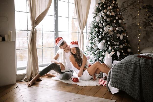 Un gars et une fille heureux en t-shirts blancs et chapeaux de père noël sont assis et s'embrassent dans la pièce par terre devant la fenêtre à côté de l'arbre du nouvel an, des cadeaux et des bougies.