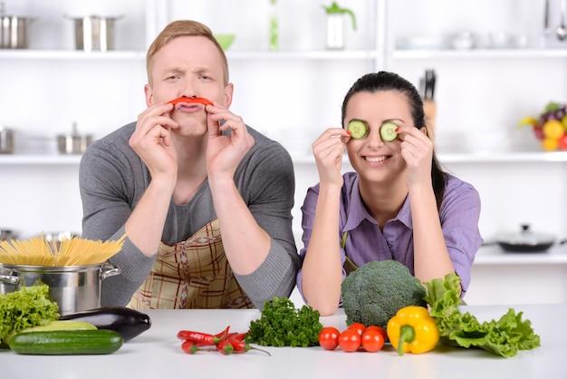 Le gars et la fille jouent dans la cuisine avec des légumes.