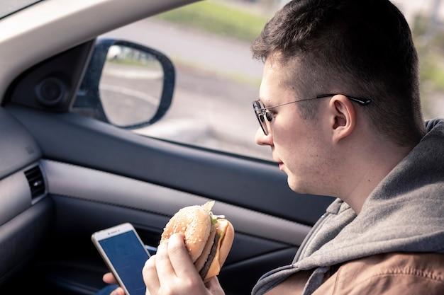 Le gars et la fille mangent de la restauration rapide assis dans la voiture et parlent de la nourriture malsaine de restauration rapide