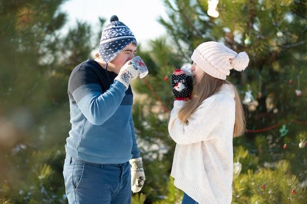 Le gars avec la fille marche et embrasse dans la forêt d'hiver avec une tasse de boisson chaude. une promenade d'hiver confortable à travers les bois avec une boisson chaude. couple d'amoureux, vacances d'hiver