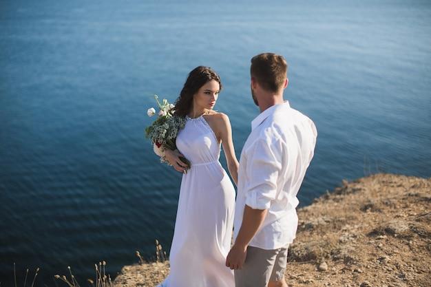 Un gars et une fille marchent sur le précipice de la montagne avec le fond de l'océan.