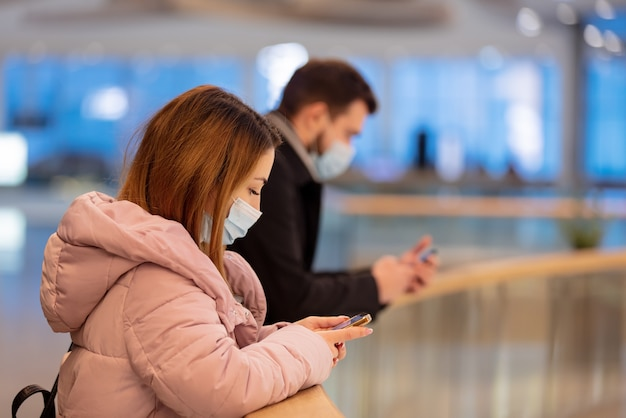 Un gars et une fille masqués utilisent un téléphone portable dans un centre commercial de la ville en temps de pandémie