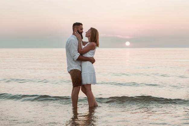 Un gars et une fille sur la mer adorent les gens dans l'eau sur la plage