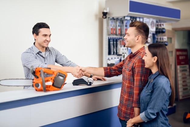 Un gars et une fille paient pour l'achat d'une scie à chaîne.