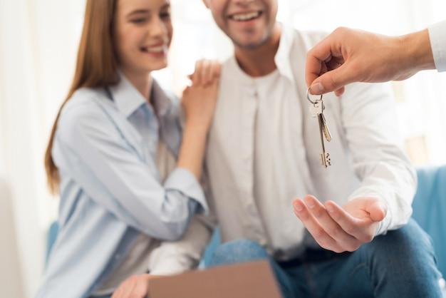 Un gars et une fille passent un contrat avec un agent immobilier qui achète une propriété.