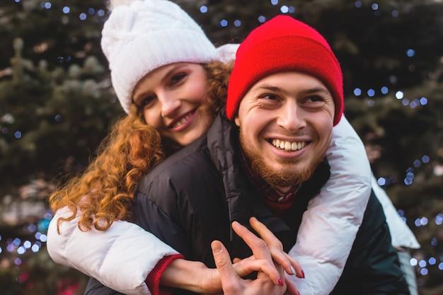 Le gars et la fille en pull rouge sourient joyeusement à l'arbre de noël.