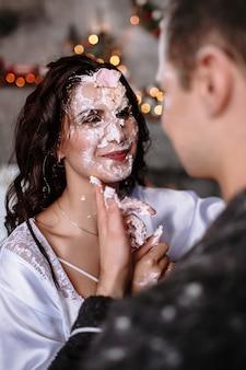 Un gars et une fille en robe de chambre dans la cuisine, enduits de crème sucrée. la cuisine est préparée pour les fêtes de noël et du nouvel an