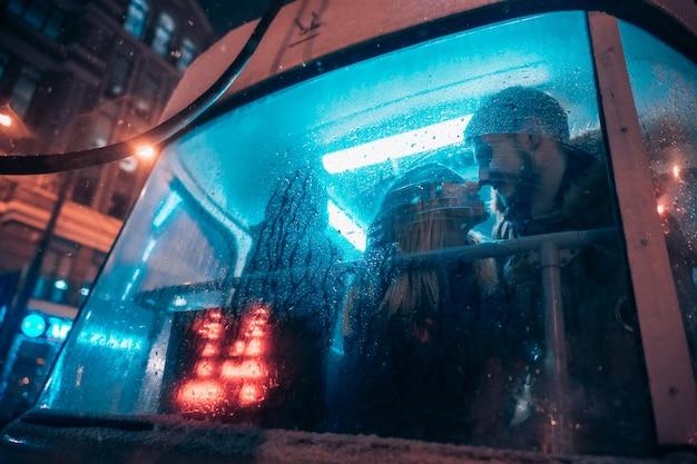 Le gars et la fille s'embrassent dans le tramway derrière le verre brumeux