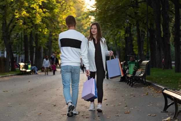 Un gars et une fille avec des sacs à provisions à la main se réunissent et se regardent.