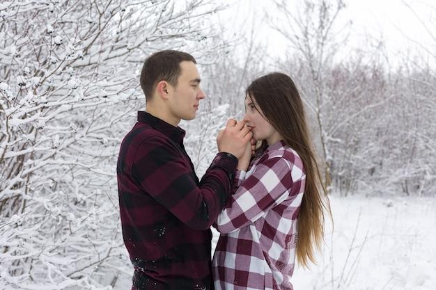 Le gars et la fille se reposent dans les bois d'hiver mari et femme dans la neige jeune couple