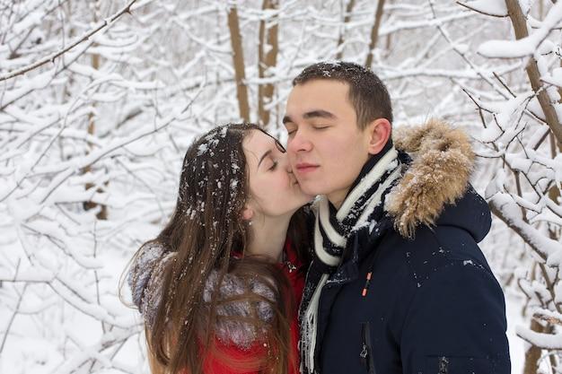 Le gars et la fille se reposent dans les bois d'hiver. mari et femme dans la neige.