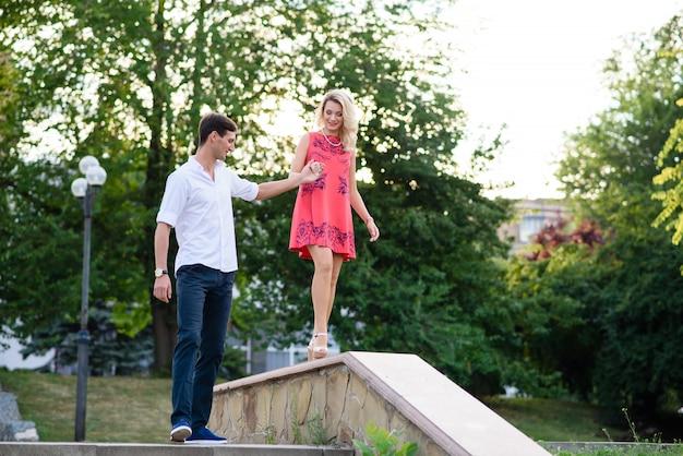 Un gars avec une fille se tenant la main dans le parc.