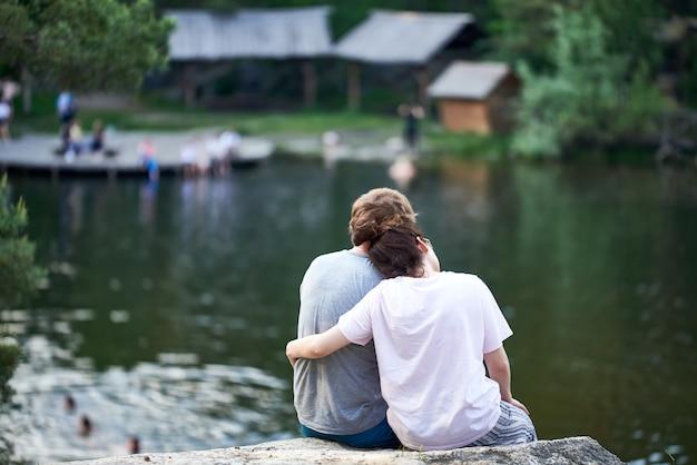 Le gars et la fille sont assis sur une falaise au-dessus de la rivière et regardent devant. vue arrière. couple d'amoureux.