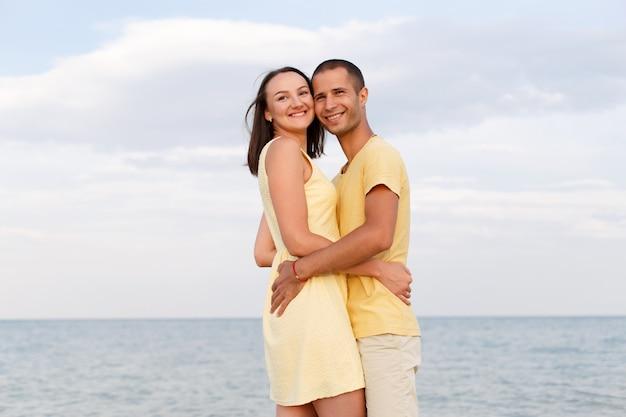 Un gars et une fille en vêtements jaunes se tiennent dans une étreinte sur la plage