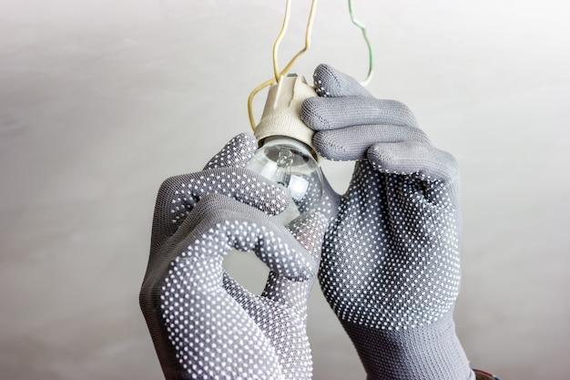 Un gars en gants gris fait tourner une ampoule en remplaçant l'ampoule