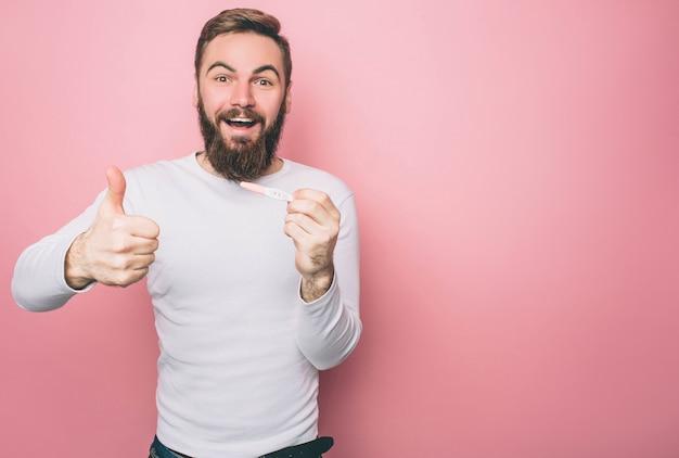Un gars heureux montre son gros pouce et un test de grossesse