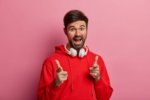 Un gars hipster barbu positif pointe directement vers vous, fait le bon choix, dit excellent, fait son geste, porte un sweat à capuche rouge et des écouteurs modernes, pose contre un mur rose pastel
