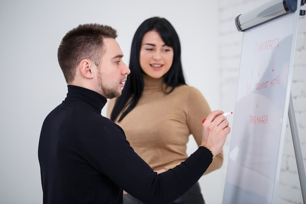 Le gars un homme d'affaires, un enseignant, un mentor enseigne une fille spécialiste, une étudiante. notion de jour ouvrable